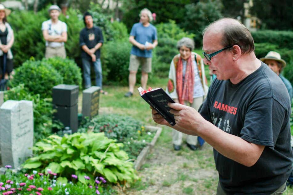 """Der Schriftsteller Peter Wawerzinek liest beim Sommerfest im Brecht-Weigel-Haus zur Veranstaltung """"Geisterstunde"""" am späten Abend auf dem Dorotheenstädtischen Friedhof am Grab des Autors Wolfgang Herrndorf."""