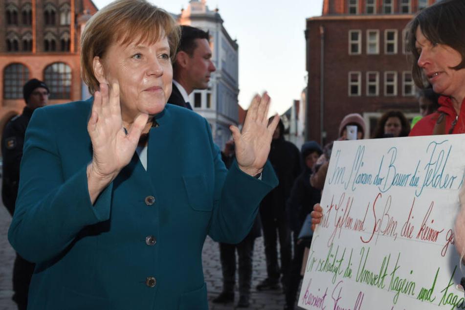 Bundeskanzlerin Angela Merkel (64, CDU) spricht vor dem Jahresempfang des Wirtschaftsrates der CDU auf dem Alten Markt mit Demonstranten einer Schülerdemo.