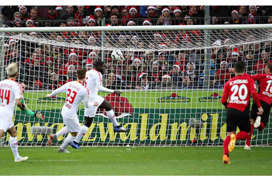 Das 1:0: Nach einem Abpraller von Péter Gulácsi (l., grünes Trikot) stochert Freiburgs Nils Petersen (r.) den Ball aufs Tor. Sowohl der Keeper als auch Ibrahima Konaté (3.v.r.) springen darunter durch.
