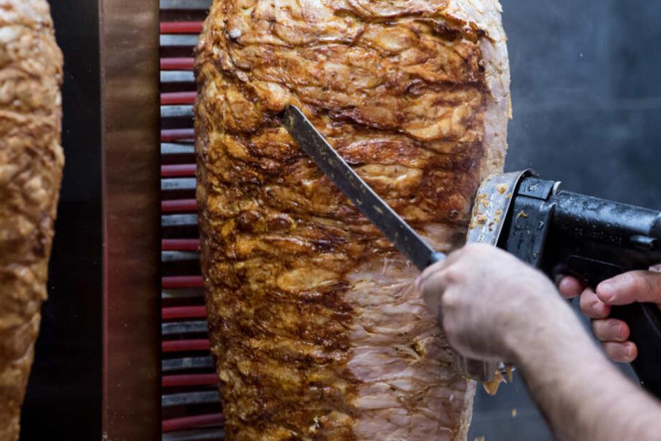 Von einem Dönerspieß wird Fleisch abgeschnitten.