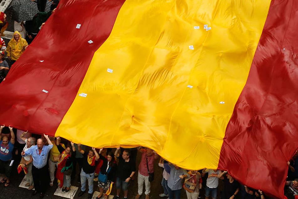 Demonstranten tragen in Barcelona (Spanien) bei einer Demonstration gegen die Unabhängigkeit Kataloniens eine riesige spanische Flagge.