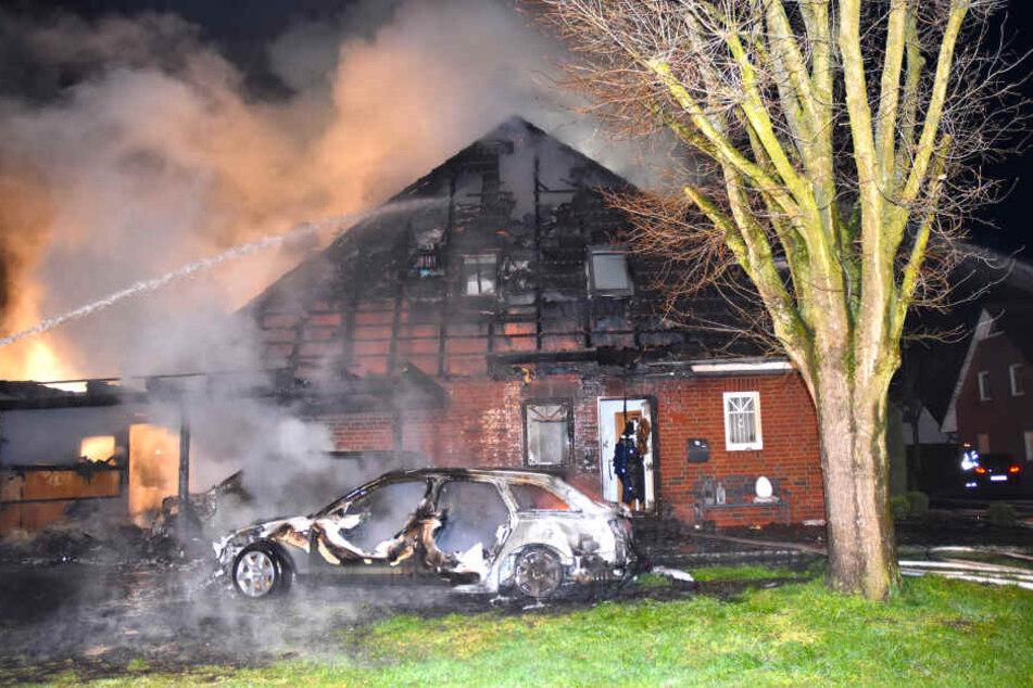 Die völlig bereits ausgebrannten Fahrzeuge und das zerstörte Wohnhaus im Ortskern von Schwanewede sind bei den Löscharbeiten zu sehen.