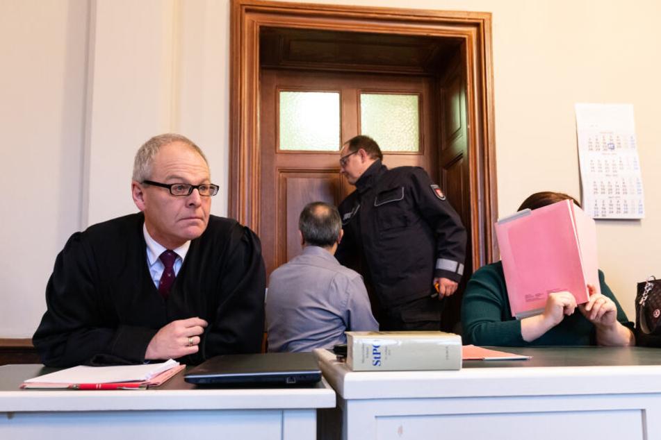 Die 48-jährige Angeklagte verdeckt im Amtsgericht neben Anwalt Uwe Bartscher ihr Gesicht.