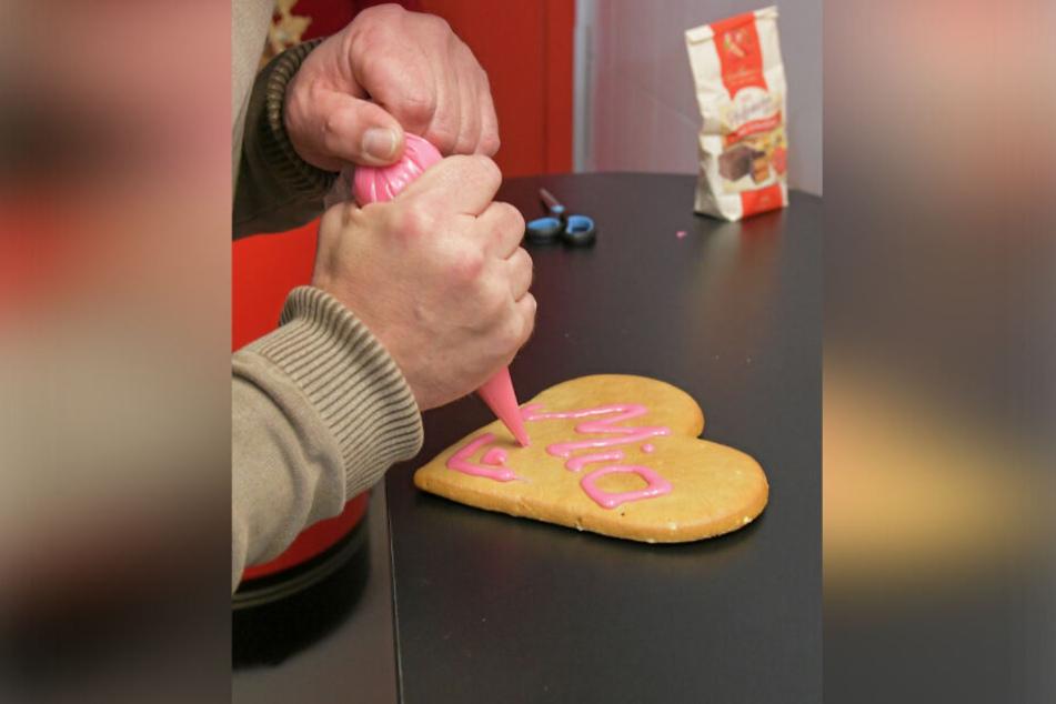 Den ersten Pfefferkuchen verziert Mia Manuela mit ihrem Namen in rosa Zuckerguss.