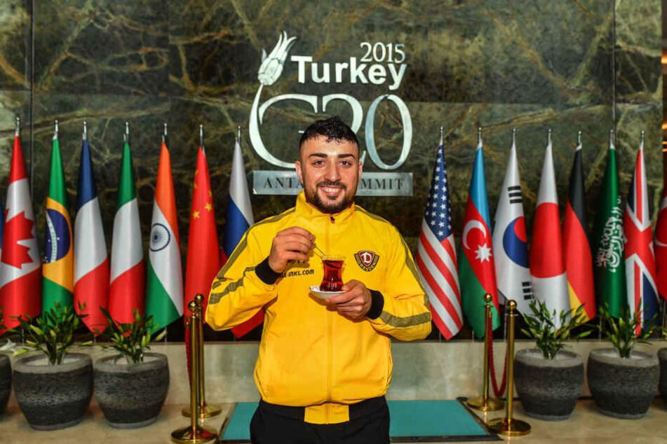 """Aias Aosman mit türkischem Tee in der Hotellobby vor den G20-Länderfahnen im Trainingslager in der Hotelanlage des """"Regnum Carya"""" Belek."""