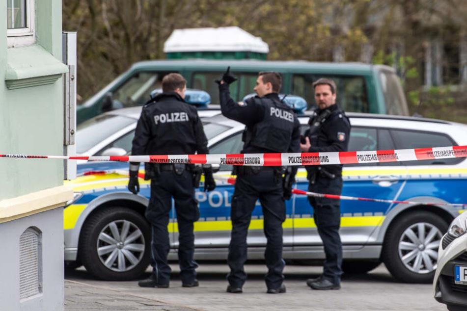 Polizeibeamte stehen vor einem Gebäude in Flensburg, in dem die tote Frau entdeckt wurde. (Archivbild)