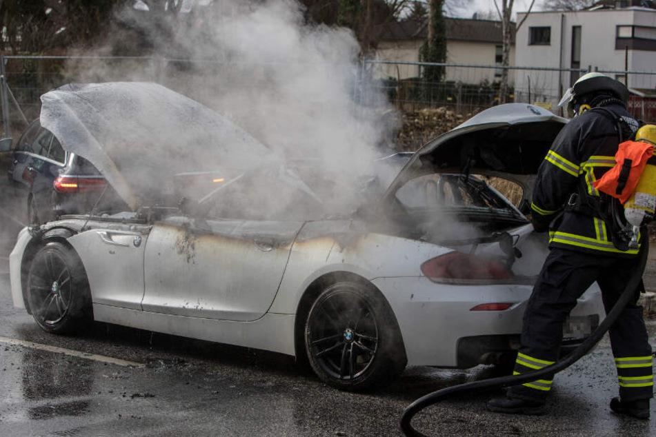 Ein Feuerwehrmann löscht den Brand im Sportwagen.