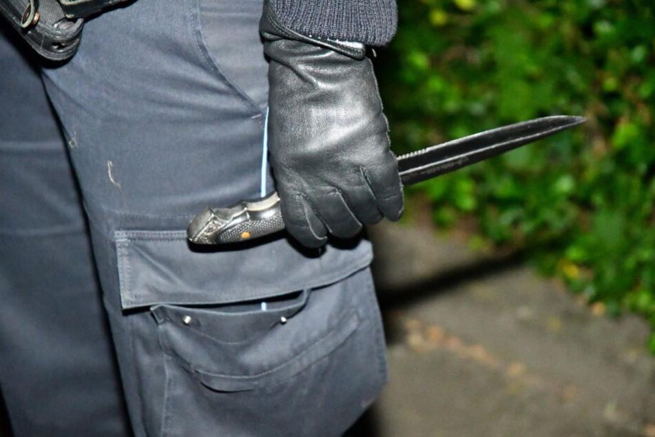 Ein Polizeibeamter hält das Messer des Tatverdächtigen in der Hand.