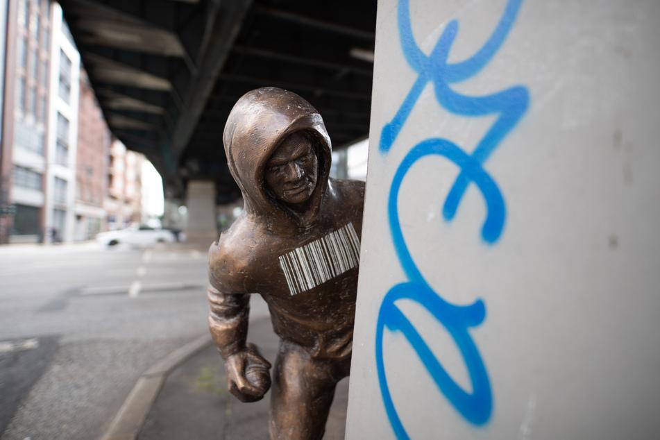 Eine Bronzestatue, die einen Mann mit Kapuzenpulli darstellt, der eine Spraydose in der Hand hält, steht am Pfeiler des U-Bahn-Viadukts am Rödingsmarkt.