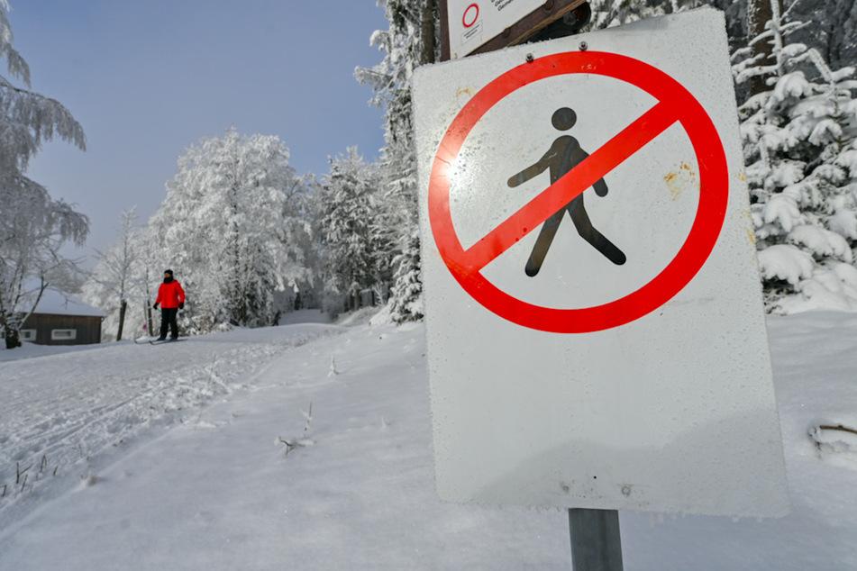 Ein Verbotsschild für Fußgänger steht auf dem Berg Rusel im Landkreis Deggendorf an einer Langlaufloipe. Zahlreiche Landkreise schließen ihre Grenzen für Tagesausflügler.