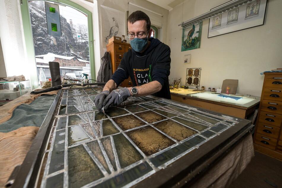 Lars Janse (40) reinigt das Glasfenster, erneuert den Kitt und die Bleiverglasung.