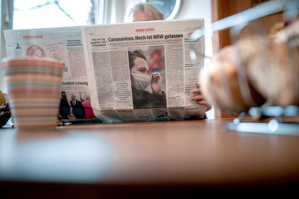 Eine Frau liest eine Zeitung am Frühstückstisch. Eine Zeitung, die beim Bäcker ausliegt, geht durch viele Hände. Vor dem Auftreten des Coronavirus war das kein Problem. Aber jetzt? Kann ich mich beim Lesen über das Papier infizieren?