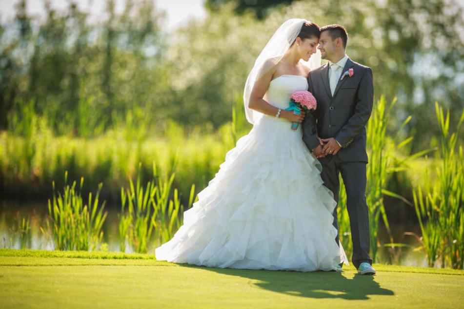 Ein Hochzeitspaar steht auf einer Wiese. (Symbolbild)