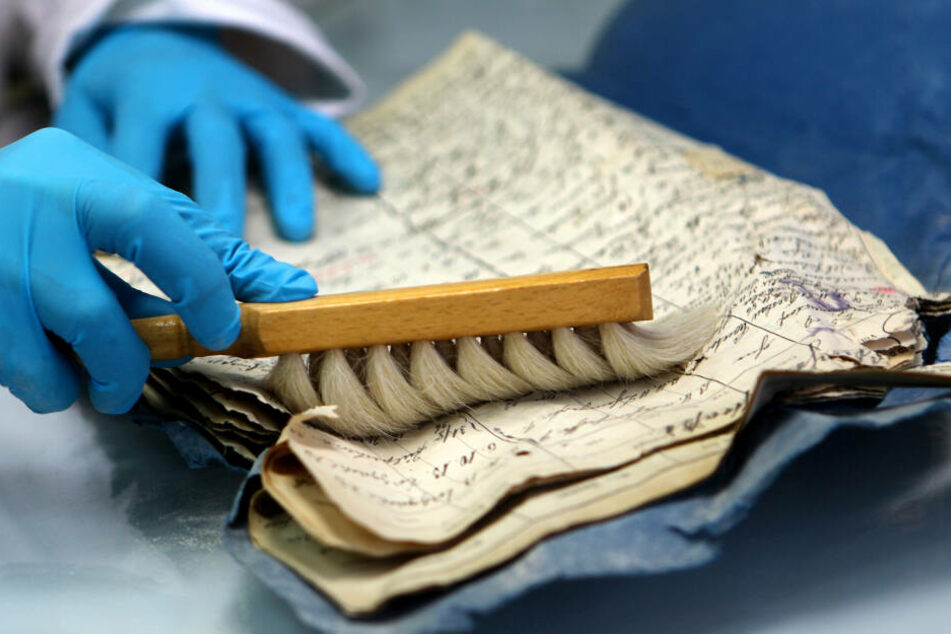 Ein Restauratorin reinigt in Köln ein historisches Dokument aus dem eingestürzten Kölner Stadtarchiv.