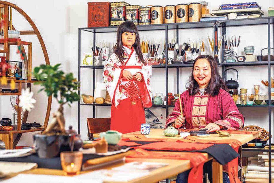 """Yini Tao (40, """"Pferd"""") und ihre Tochter Lisa Duoya (6, """"Drache"""") stecken voll in den Neujahrsvorbereitungen. Frau Tao ist Kalligrafie-Meisterin (F.u.)."""