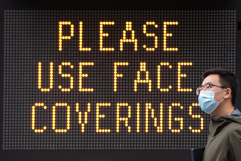 Ein Mann mit Mundschutz geht in der Nähe der Londoner Tower Bridge an einer Anzeige vorbei, die die Menschen bittet einen Gesichtsschutz zu benutzen.