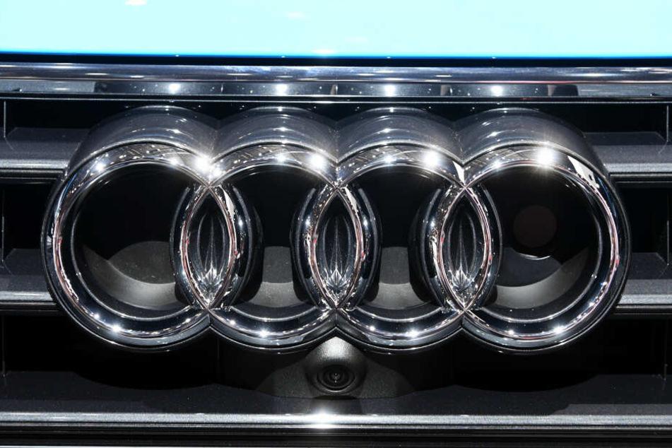 Ein Audi Logo an einem Kühlergrill; in Zukunft will Audi vor allem auf Hybrid und Elektroautos setzten.