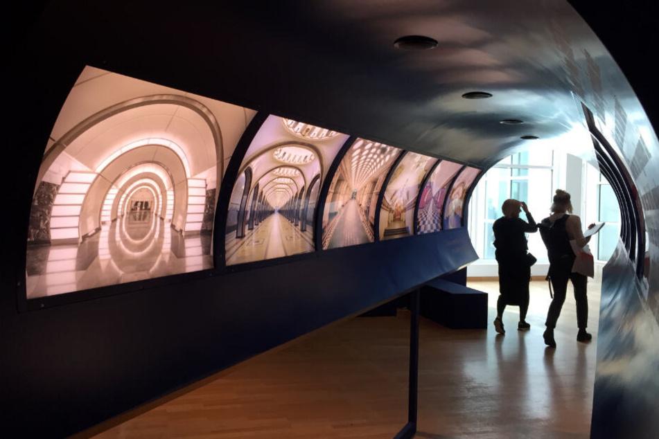 Besucher laufen im Museum für Angewandte Kunst an rückwärtig beleuchteten Fotografien von Bahnhöfen vorbei.