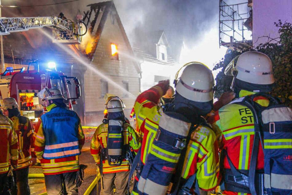 Feuerwehrleute löschen das brennende Haus.