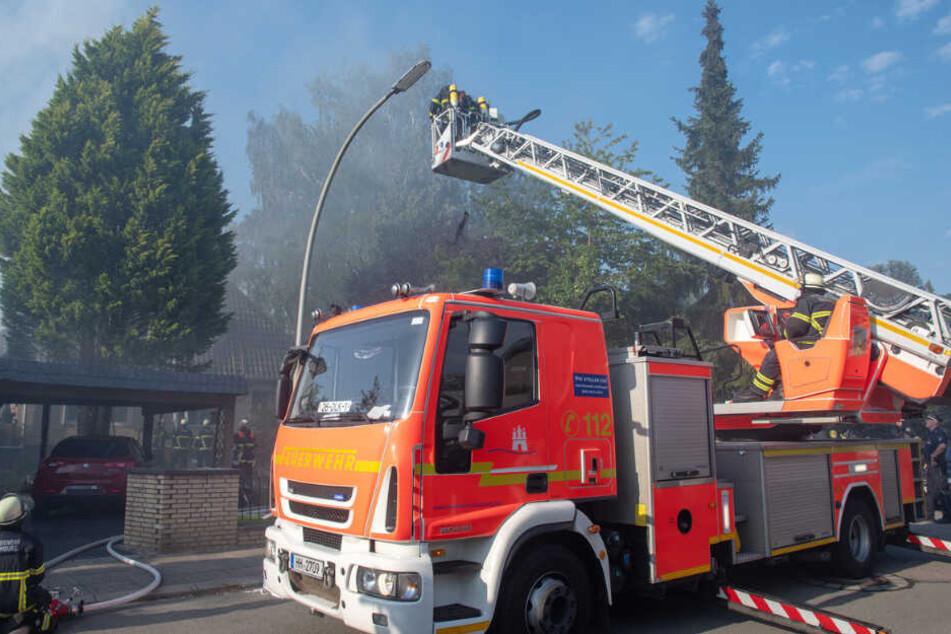 Feuerwehrleute löschen ein brennendes Haus in Hamburg von der Drehleiter aus.