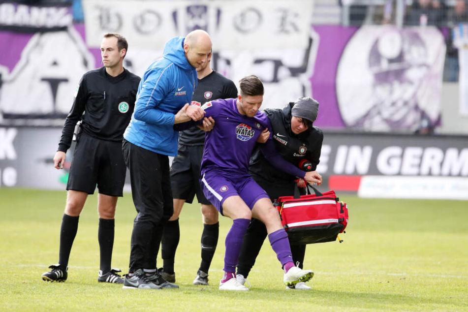 Im Februar beim 0:3 daheim gegen Ingolstadt verletzte sich Dennis Kempe schwer am Knie. Er wird hier von Mannschaftsarzt Stephan Rezmann (l.) und Physiotherapeutin Marie Koch (r.) vom Feld geführt.