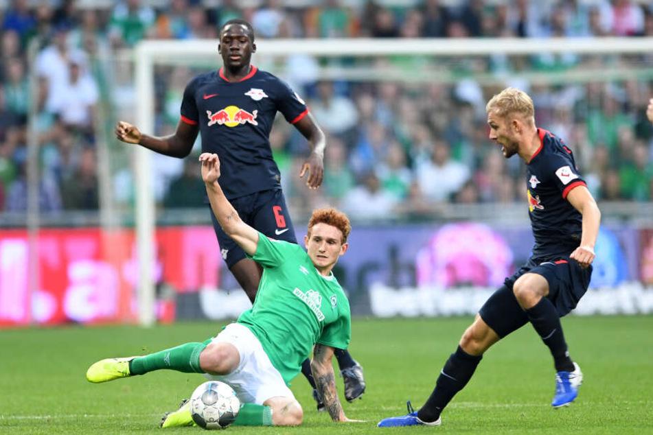 Werders Josh Sargent (M) grätscht den Ball vor Leipzigs Ibrahima Konate und Konrad Laimer (r) weg. Das Hinspiel war eine umkämpfte Angelegenheit.