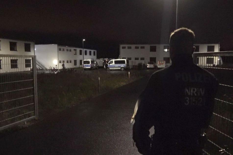 Ein Polizist steht am Tor zu einer Flüchtlingsunterkunft in dem Ort.