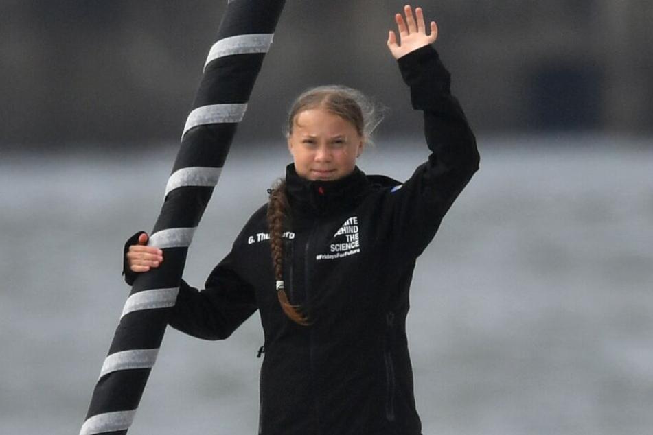 """Greta Thunberg winkt von Bord der Hochseejacht """"Malizia""""."""