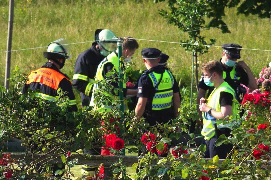Die Rettungskräfte stehen um den Unfallort herum.