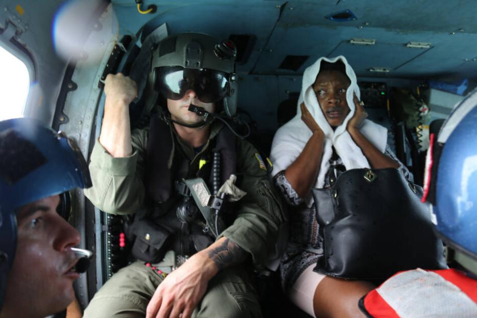 Ein Mitglied der US-Küstenwache sitzt neben einer verletzten Überlebenden, die nach dem Hurrikan Dorian von Marsh Harbour auf Great Abaco Island per Hubschrauber evakuiert wird.