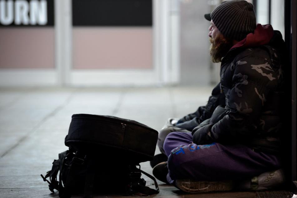 Zwei Obdachlose sitzen in Stuttgart in einer Unterführung.