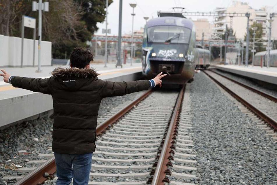 Ein Mann stellt sich auf die Gleise am Bahnhof Athen-Larisa, der von Migranten blockiert wurde, vor einen herannahenden Zug.