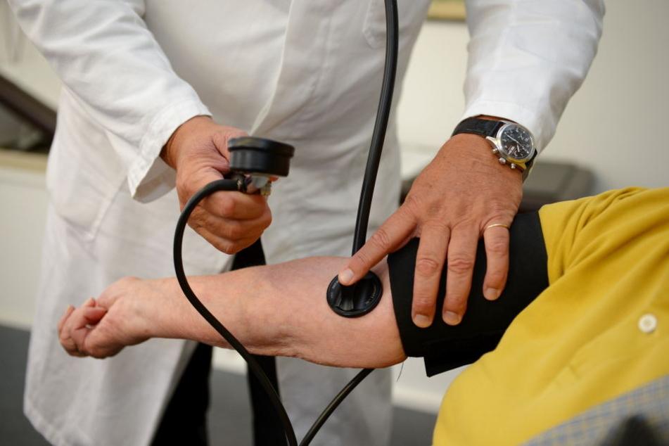 Ein Arzt misst in seiner Praxis  einer Patientin den Blutdruck. (Symbolbild)