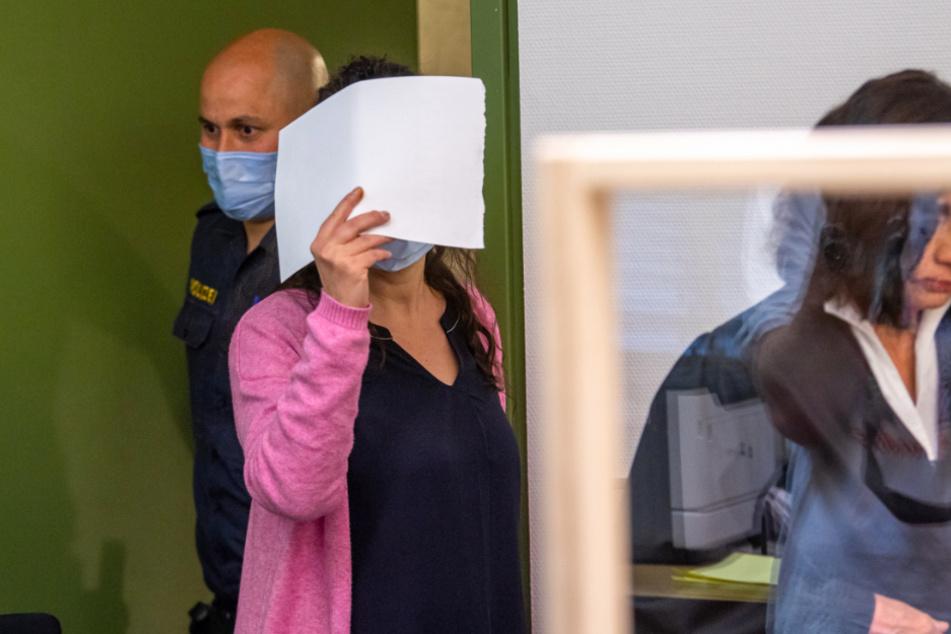 Die Angeklagte wird vor Prozessbeginn zu ihrem Platz im Verhandlungssaal gebracht. Rechts steht ihre Anwältin Marina Hamel.
