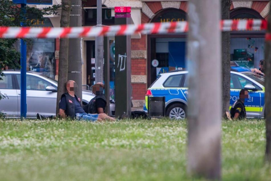 Nach der Schießerei auf der Eisenbahnstraße sitzen festgenommene Hells Angels mit gefesselten Händen in einer Parkanlage. Vier wurden bereits wegen gemeinschaftlichen Mordes zu lebenslanger Haft verurteilt.