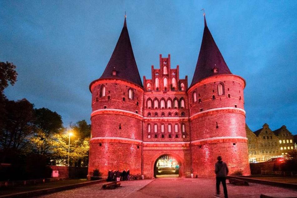 Das Lübecker Holstentor leuchtet in der Farbe Pink.