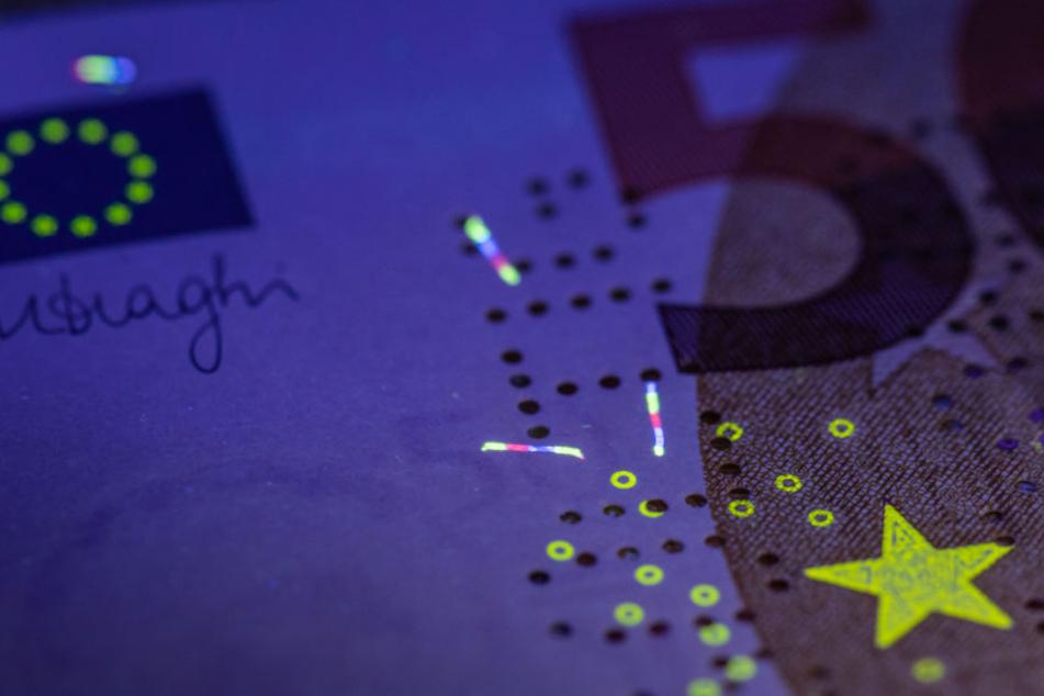 Unter einer UV-Lampe werden in der Zentrale der Deutschen Bundesbank die in das Papier einer echten 50-Euro-Banknote eingearbeiteten Sicherheitsfasern mehrfarbig zum Leuchten gebracht. (Symbolbild)