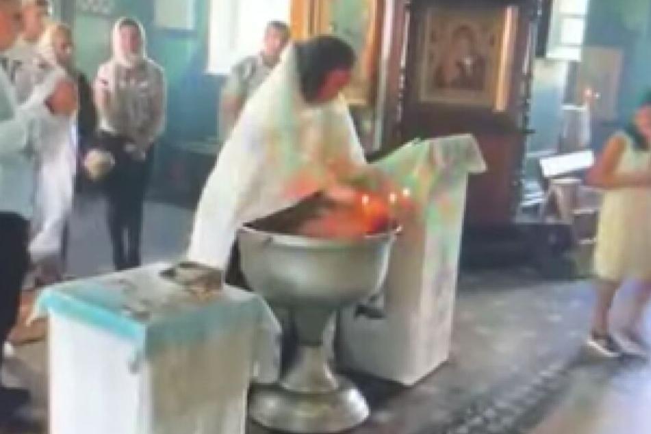 Der Priester drückt das schreiende Baby mit der Hand auf seinem Gesicht unter Wasser.
