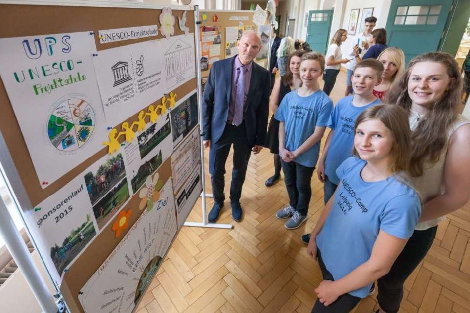 Schuldirektor Ralf Ballmann (55) und Schüler der Klasse 8a vor einer Ausstellungstafel zu den Projekten der Schule.