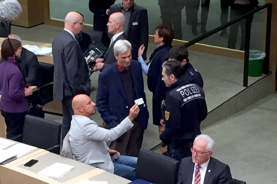 Stefan Räpple (sitzend, l.), Abgeordneter der AfD im Landtag von Baden-Württemberg, spricht während einer Plenarsitzung mit Polizisten. Zuvor hater sich geweigert, trotz Aufforderung der Landtagspräsidentin, den Saal zu verlassen. In der Mitte steht Wolfg