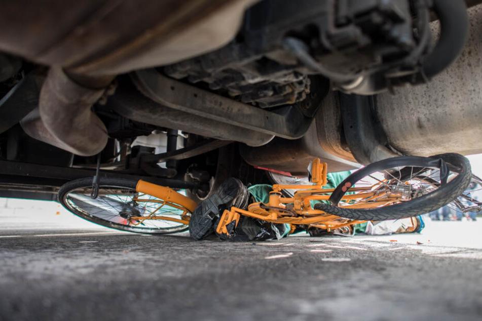 Ein Fahrrad liegt nach einem Unfall völlig zerstört unter einem Lastwagen. (Symbolbild)