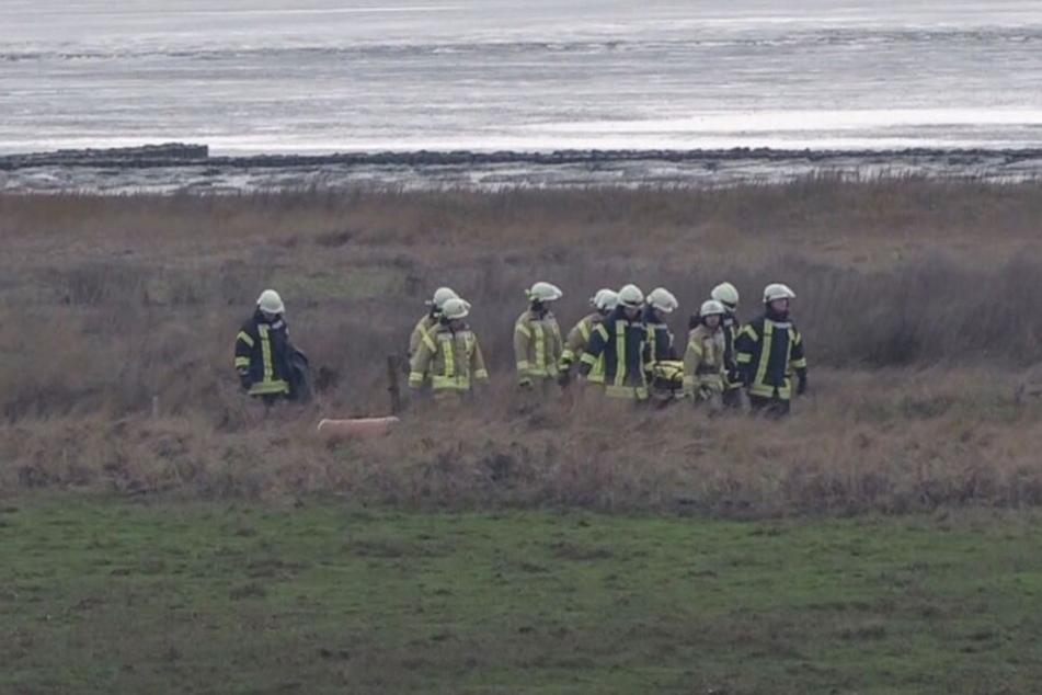 Feuerwehrleute gehen mit der Leiche auf einer Trage am Deich entlang.