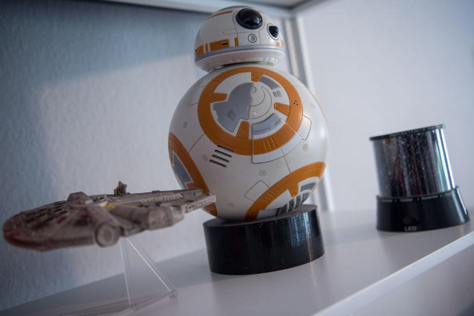 """Fans von """"Star Wars"""" erkennen sie sofort: das Raumschiff """"Millenium Falke"""" und der Droide BB-8 stehen im Regal der Cosplayerin."""