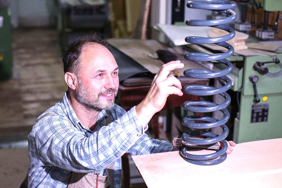 Erfinder Wollmann mit einer der massiven Federspiralen für die Babywiege.