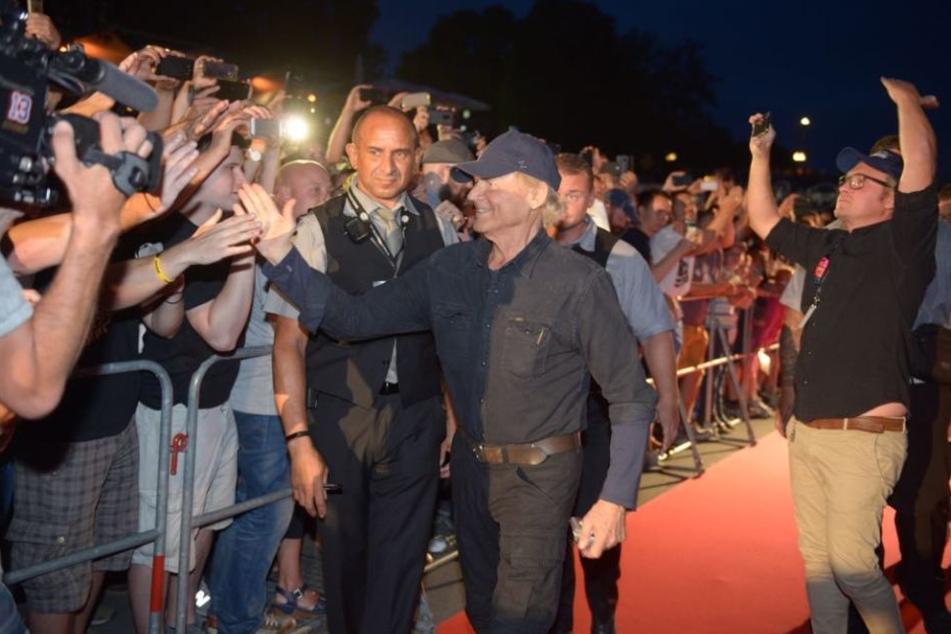 Der Schauspieler klatscht mit seinen Fans auf dem roten Teppich ab.
