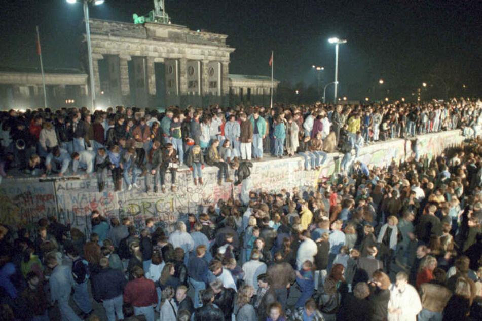 Menschen auf der Berliner Mauer vor dem Brandenburger Tor in der Nacht vom 9. auf den 10.11.1989. (Archivbild)