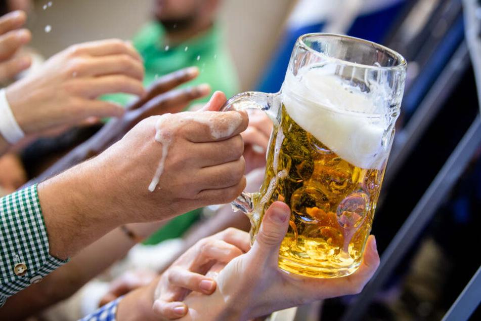 Besucher greifen im Paulaner-Festzelt nach einem Bierkrug.