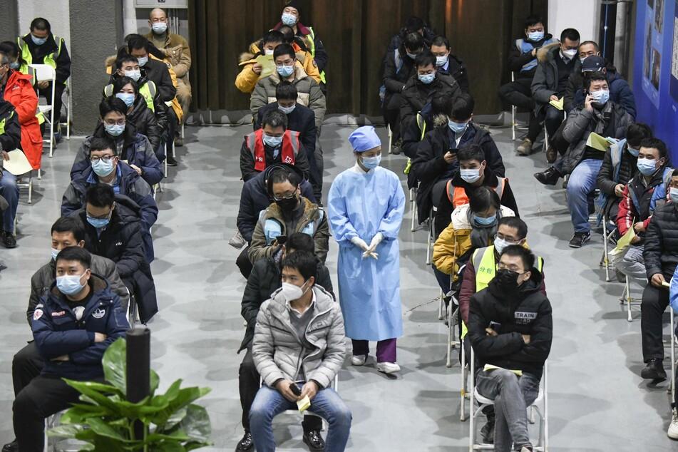 Peking: Eine Medizinerin geht zwischen Menschen mit Mund-Nasen-Bedeckung entlang, die gerade eine Impfdosis mit einem Corona-Impfstoff erhalten haben und nun 30 Minuten warten müssen, um zu sehen, ob sie Reaktionen zeigen.