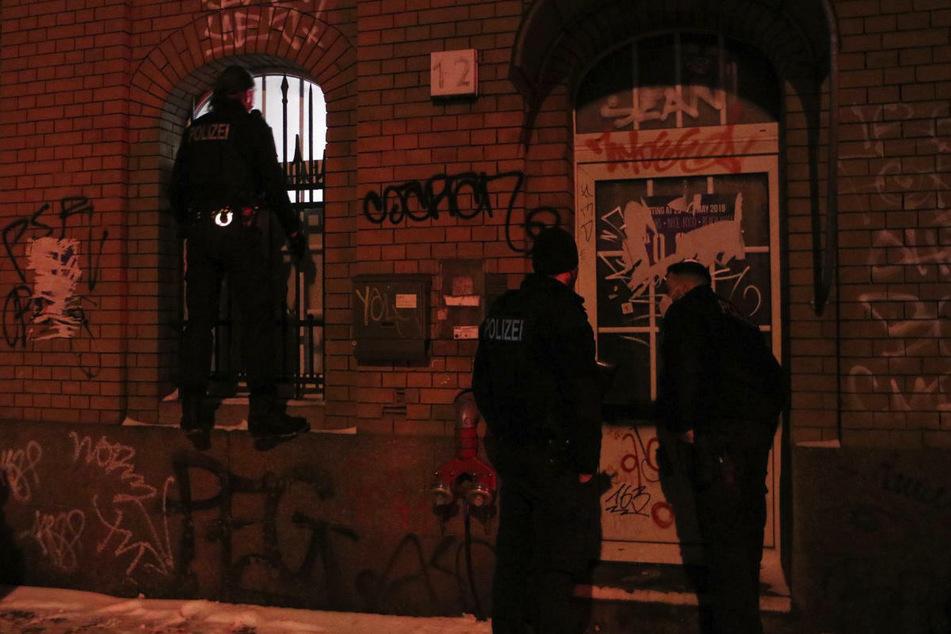 Ein Polizeibeamter versucht durch ein Fenster des Clubs einen Blick auf die Vorgänge im Inneren zu erhaschen, während zwei Kollegen an der Tür warten.
