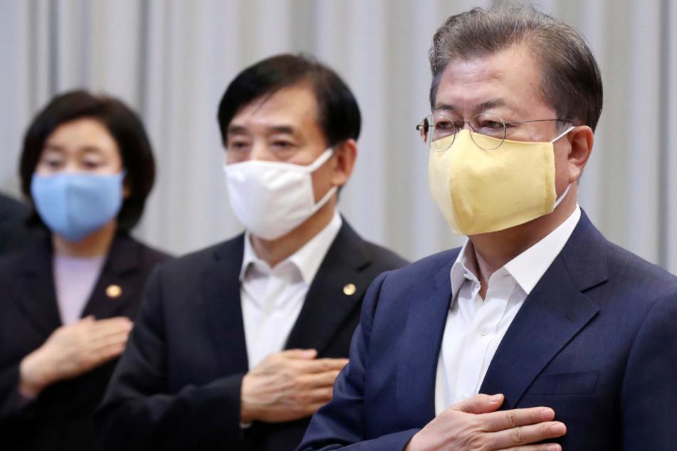 Moon Jae In (r.), Präsident von Südkorea, und Lee Ju Yeol (M.), der südkoreanische Gouverneur der Bank of Korea, tragen Mundschutzen und salutieren vor einer Nationalflagge bei einem wirtschaftlichen Notfalltreffen im Blauen Haus des Präsidenten.